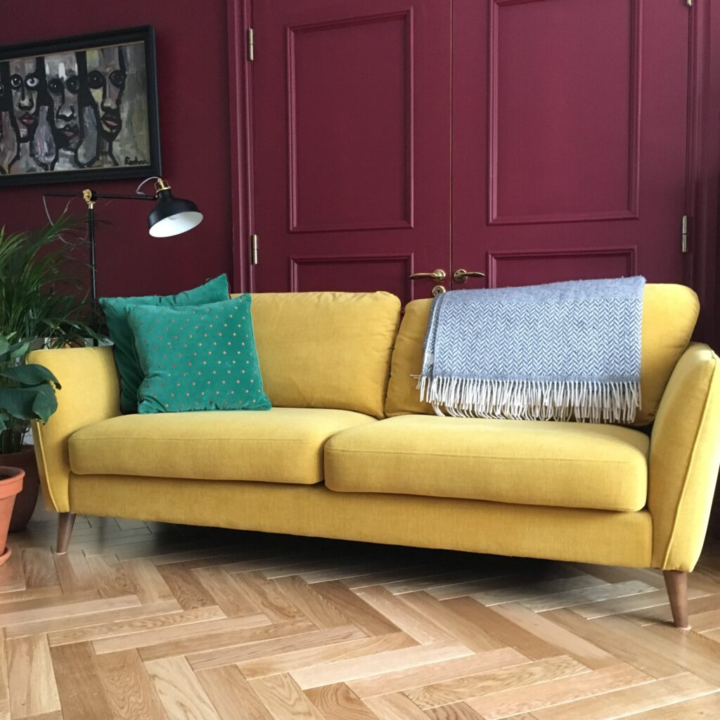 Mustard sofa against wine doors