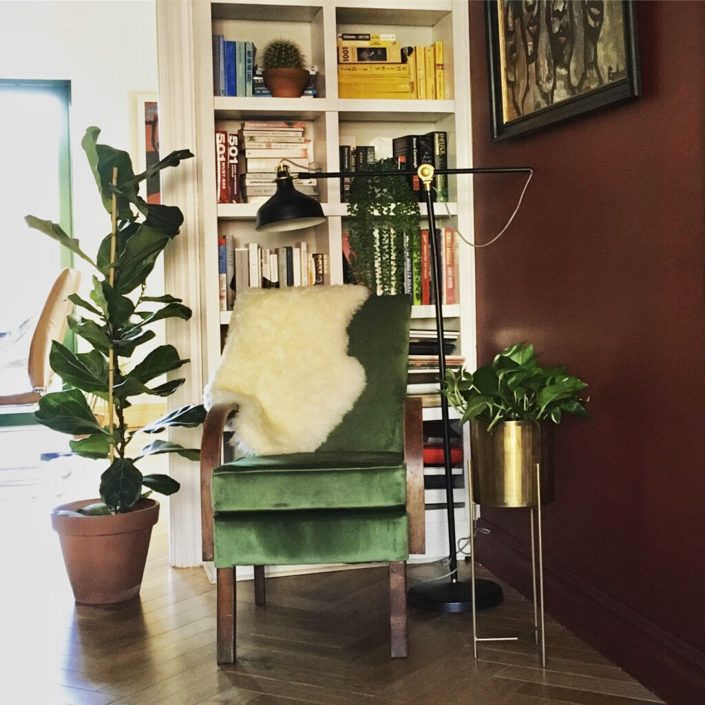 Green chair with sheepskin in front of bookshelf