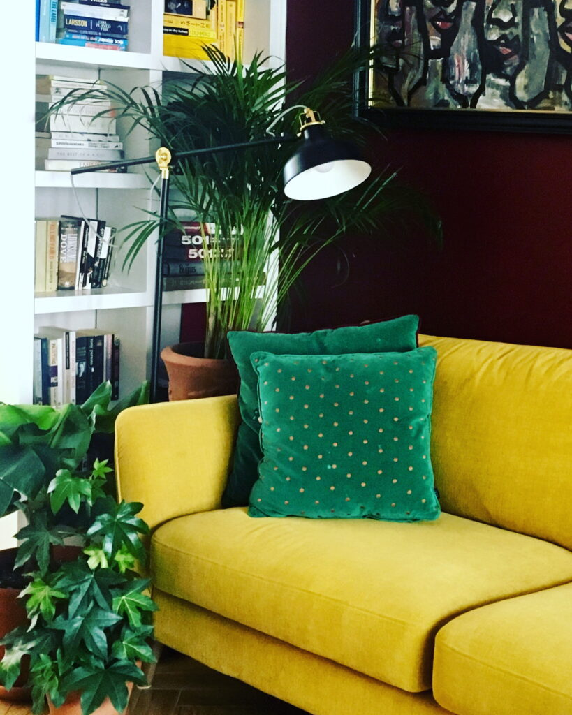 Mustard sofa with green cushions and house plants