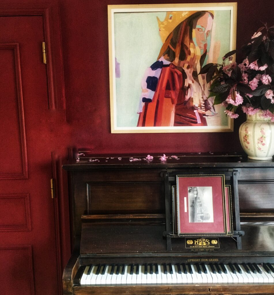 Dark wood piano against wine wall