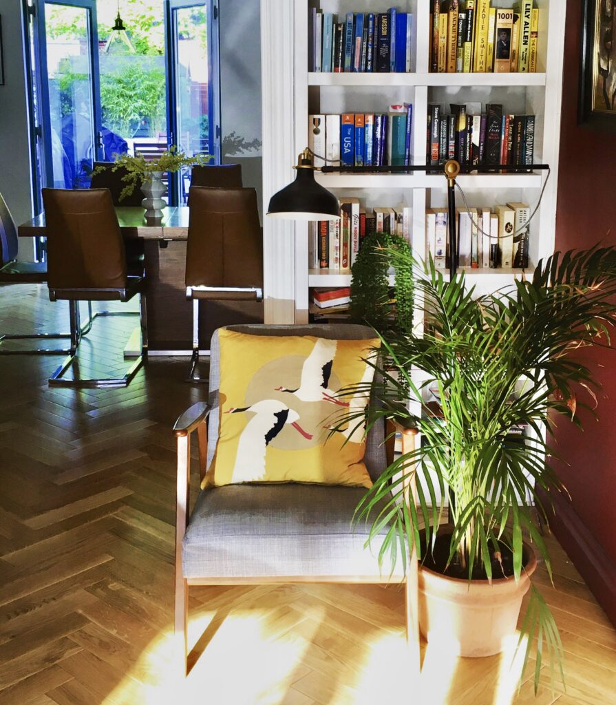 Reading nook with grey chair and house plants